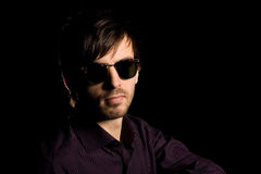 Stylish young man wearing sunglasses. Portrait of a stylish young man wearing sunglasses on a black background Stock Image