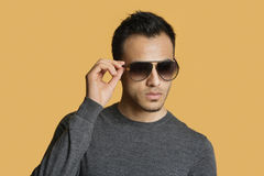 Stylish young man wearing sunglasses over colored background Royalty Free Stock Images