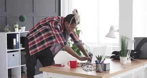 Stylish young man working on laptop at office desk. Casual african american businessman working on laptop at office desk stock video