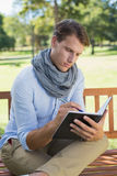 Stylish young man writing in his notepad Royalty Free Stock Images