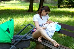Stylish young mom parent is nursing the beautiful baby surrounded by green grass in the public park, lady is breastfeeding infant royalty free stock photos
