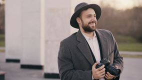 Stylish young photographer man in hat standing outdoors and photographing tourist sightseeings during travel royalty free stock image