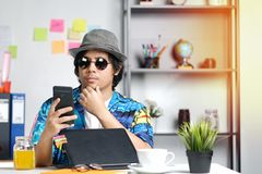 Stylish Young Professional Checking Smartphone While Working on. Summer Vacation at Office Stock Photos