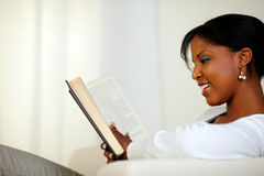 Stylish young relaxed woman reading a book Stock Image