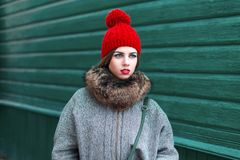 Stylish young Russian girl in fashionable winter clothes standin. G near a green wooden wall Royalty Free Stock Photo