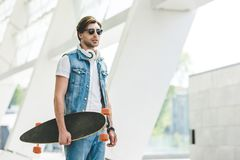 Stylish young skater in denim clothes with longboard. And headphones stock image