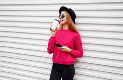 Stylish young smiling woman drinks coffee holds phone in pink knitted sweater on white wall stock image