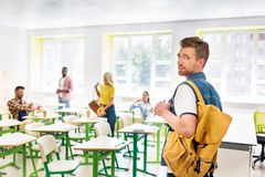 stylish young student in classroom of college with blurred classmates stock photos