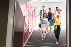 stylish young students walking down on stairs of royalty free stock images