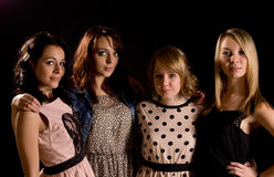 Stylish young teenage girls on a night out. Four stylish young teenage girls on a night out pose in a line in their trendy party clothes on a dark background Stock Images