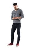 Stylish young trendy man typing message on cellphone. Full body length portrait isolated on white studio background Royalty Free Stock Photography