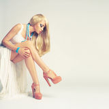Stylish young woman. Beautiful young woman sitting in a trendy shoes Royalty Free Stock Photography