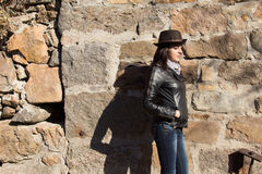 Stylish young woman against an old stone wall Royalty Free Stock Photos