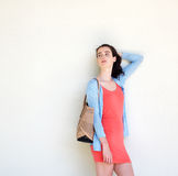 Stylish young woman carrying a purse leaning against wall Stock Photo
