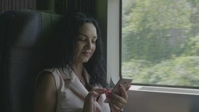 Stylish young woman commuting on train smiling while she browsing internet surfing on social media network on smartphone -. Stylish young woman commuting on stock video footage