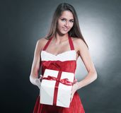 Stylish young woman in costume of Santa Claus with Christmas gif. T . isolated on a black background Stock Images