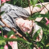 Stylish, young woman, dreamily lying on the grass royalty free stock image