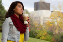 Stylish young woman enjoying coffee during fall with the city in royalty free stock images