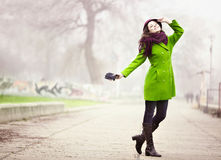 Stylish Young Woman in the Foggy Autumn Day. Portrait of Happy Young Woman Standing at the Walkway in the Foggy Autumn Day Royalty Free Stock Photography