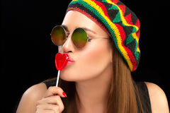 Stylish Young Woman Kissing a Heart Shaped Lollipop Royalty Free Stock Image