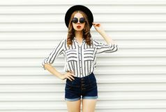 Stylish young woman model in black round hat, shorts, white striped shirt posing on white wall. Background royalty free stock images