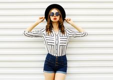 Stylish young woman model in black round hat, shorts, white striped shirt posing on white wall. Background stock photos
