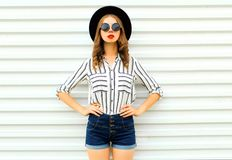 Stylish young woman model in black round hat, shorts, white striped shirt posing on white wall. Background royalty free stock photo