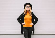 Stylish young woman model wearing black style clothes, coat, round hat, posing on city street. Gray wall background stock photography