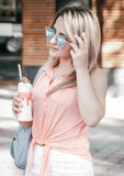 Stylish woman outdoor with a coctail. Stylish young woman outdoor with a coctail Stock Images