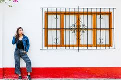 Stylish young woman posing against window outdoors. Fashionable outfit. stock photos