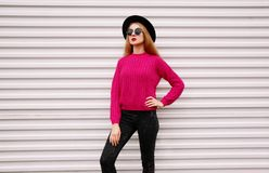 Stylish young woman posing in colorful pink knitted sweater, black round hat on white wall. Background royalty free stock photo