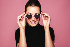 Stylish young woman posing with funky shades. Portrait of stylish young woman with heart shaped sunglasses over pink background. Caucasian fashion model posing stock photos