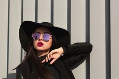 Stylish young model posing in mirror glasses and broad brimmed h. Stylish young woman posing in mirror glasses and broad brimmed hat. Female fashion concept Royalty Free Stock Image