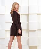 Stylish young woman posing. Near futuristic white wall Royalty Free Stock Photography
