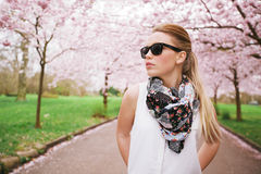 Stylish young woman posing at the spring blossom garden. Royalty Free Stock Photos