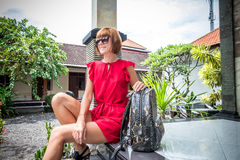 Stylish young woman in red dress with leather snakeskin python rucksack in the asian garden. Tropical Bali island Royalty Free Stock Photography