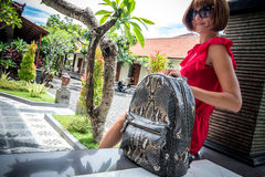 Stylish young woman in red dress with leather snakeskin python rucksack in the asian garden. Tropical Bali island Royalty Free Stock Photos
