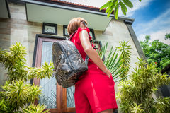 Stylish young woman in red dress with leather snakeskin python rucksack in the asian garden. Tropical Bali island Stock Photo
