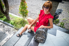 Stylish young woman in red dress with leather snakeskin python rucksack in the asian garden. Tropical Bali island Stock Photography