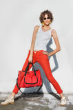Stylish young woman in red jeans with bag Stock Photo