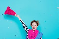 Stylish young woman removes a knitted pink hat from her head in the studio on a blue background. Winter goodbye. Spring comes. Lif Stock Photos