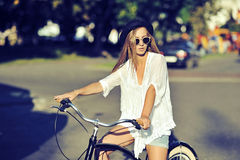 Stylish young woman on a retro bicycle. Outdoor fashion portrait Stock Photos