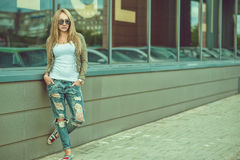 Stylish young woman in ripped jeans in front of city mall. stock photos