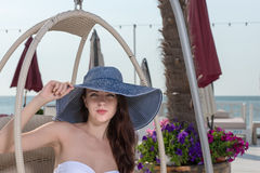 Stylish young woman sitting at a seaside resort royalty free stock photos