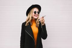 Stylish young woman with smartphone using voice command recorder or calling. Wearing black jacket, round hat on gray wall background stock photography