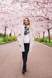 Stylish young woman at spring blossom park. Full length portrait of stylish young woman walking at spring park. Fashionable female model at spring blossom park Royalty Free Stock Photo