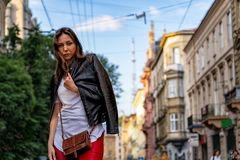 Stylish young woman is standing on the street of Lviv. Street fashion photography with beautiful girl