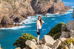 Stylish young woman standing at the very edge of the rock and staring into the distance. The place where the earth ends and the sea begins, Cabo da Roca Cape Stock Images