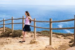 Stylish young woman standing at the very edge of the rock and staring into the distance. The place where the earth ends and the sea begins, Cabo da Roca Cape Royalty Free Stock Images