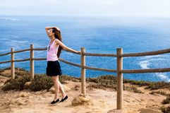 Stylish young woman standing at the very edge of the rock and staring into the distance. The place where the earth ends and the sea begins, Cabo da Roca Cape Royalty Free Stock Image